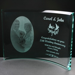 A special 10mm Curved Clear Glass Frame which is self-supporting, engraved for a 25th Wedding Anniversary, with an image of the couple and suitable text to commemorate the Wedding Anniversary.